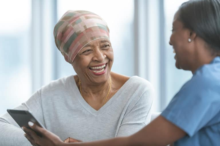 A stock photo of a patient posing with her caregiver
